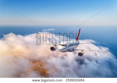 Passenger Airplane Flying Over Clouds At Sunset. Landscape With Big White Airplane, Low Clouds, Sea,
