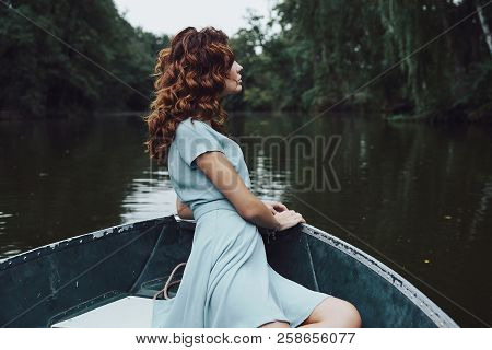 Quite Contemplation. Beautiful Young Woman In Elegant Dress Looking Away While Sitting In The Boat