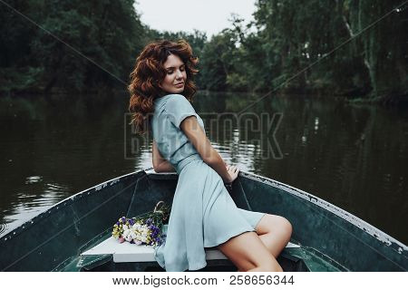 Enjoying Carefree Day. Beautiful Young Woman In Elegant Dress Smiling While Sitting In The Boat