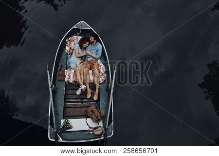 Loving Couple In Boat. Top View Of Beautiful Young Couple Embracing And Smiling While Lying In The B
