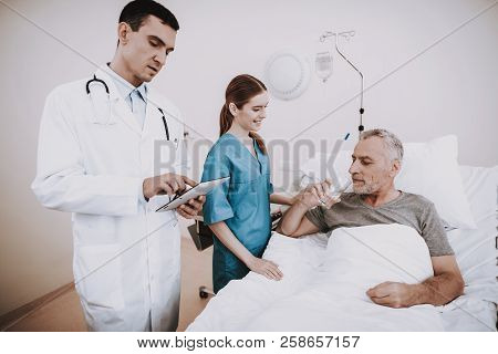 Doctor With Patient.old Man Lies In Hospital. Sick Man In Clinic. Doctor And Patient. Young Doctor W