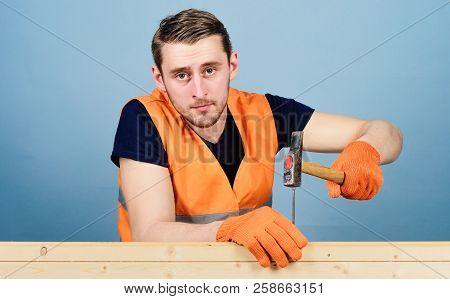 Handyman Concept. Carpenter, Woodworker On Calm Face Hammering Nail Into Wooden Board. Man, Handyman
