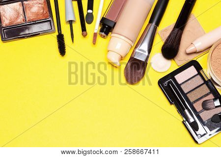 Makeup Products Bronze And Golden Colors For Casual Everyday Make-up On Yellow Background. Side Fram