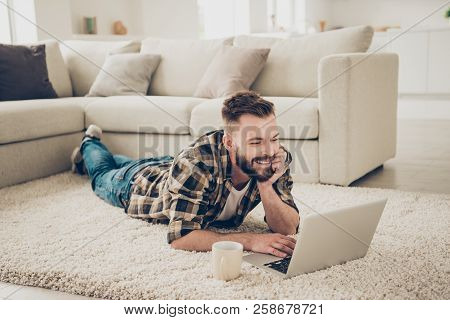 Attractive Smiling Chill Guy Is Browsing At His Laptop, Laying On The Carpet, Floor At Home On The C