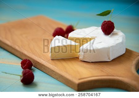 Cheese Camembert With Raspberries And Grapes On Blue Background