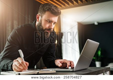 Young Bearded Businessman Is Standing By Computer, Looking At Laptop Screen, Making Notes In Noteboo