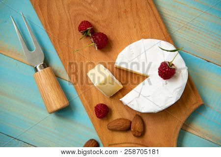 Cheese Camembert With Raspberries And Nuts, Melange On Blue Background