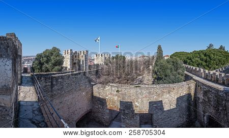 Lisbon, Portugal - February 1, 2017: Castelo de Sao Jorge aka Saint George Castle. Defensive walls with a view of the wallwalk, battlements, ramparts, merlons and crenels in the towers