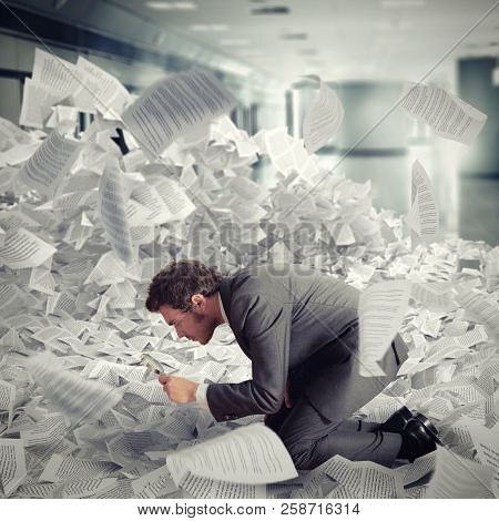 Businessman Looking With Magnifying Glass In The Middle Of A Flood Of Sheets