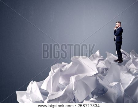 Thoughtful young businessman standing on a pile of crumpled paper with a light grey background