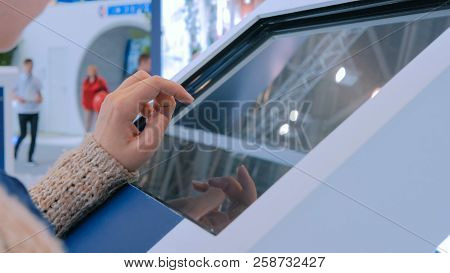 Woman Using Interactive Touchscreen Display At Urban Show
