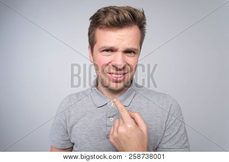 Indignant Young Male Points At Himself Isolated Over White Concrete Background.