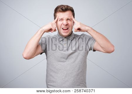 Nervous Caucasian Guy Pressing His Temples With Fingers
