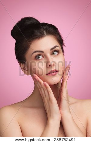 Charming Young Woman With Soft Tender And Clean Skin Touching Face And Looking Away On Pink Backgrou