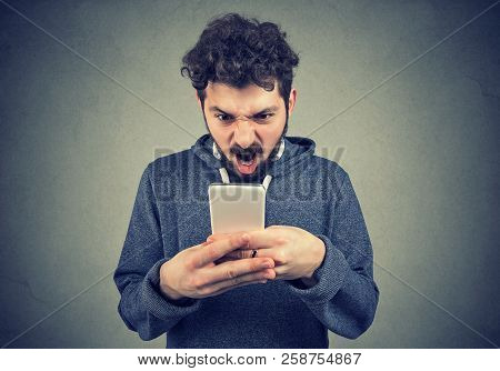 Frustrated Angry Young Man Reading A Text Message On His Smartphone Feeling Frustrated