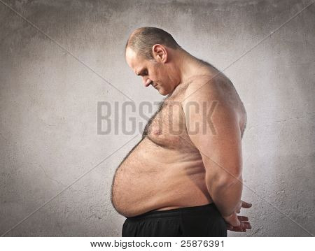 Sad fat man looking at his tummy