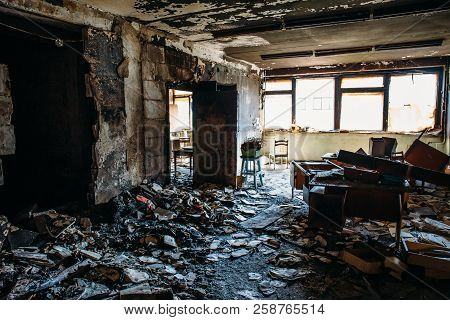 Burnt House Interior. Burned Room In Industrial Building, Charred Furniture And Damaged Apartment Af