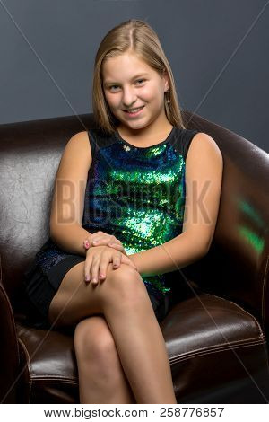 Beautiful Teen Girl Sits In The Studio On A Leather Chair. Concept Of Youth Fashion And Culture.