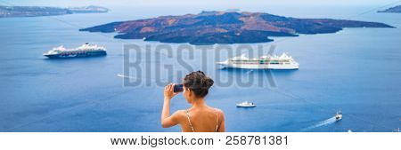 Europe Mediterranean vacation travel tourist taking holiday photo with phone of cruise ships in Aegean sea in Oia, Santorini, Greece. Europe vacation destination panoramic banner.