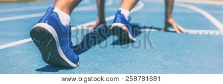 Sprinter waiting for start of race on running tracks at outdoor stadium. Sport and fitness runner man athlete on blue run track with running shoes. Banner panorama.