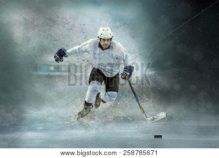 Caucassian ice hockey Player in dynamic action in a professional sport game play on the laptop in hockey under stadium lights.
