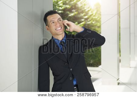 Portrait Of Asian Businessman Relax While Talking On The Phone Outside Office Room