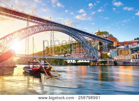 Porto old town, Portugal. Evening sunset with sunshine. Panoramic view at Ponte de Dom Luis on Douro river. Medieval monastery fort Mosteiro da Serra do Pilar. Traditional boats with port wine.