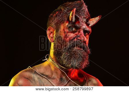Halloween holiday celebration, cosplay. Man demon on black background. Satan with beard, red blood, wounds on face. Hell, death, evil, horror concept. Devil with bloody horns on head. poster