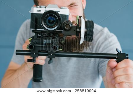 cameraman profession. lifestyle and hobby. man shooting footage using camera on holder. modern equipment and tools for video streaming concept. poster