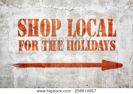 Shop local for the holidays - red graffiti sign with arrow on a white stucco wall