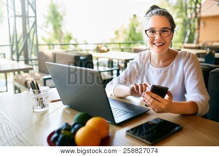 Young Mixed Race Woman Working With Laptop In Cafe Looking At Camera. Asian Caucasian Female Studyin