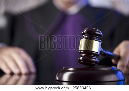 Judge In The Courtroom. Male Judge Striking The Gavel. Glass Table.