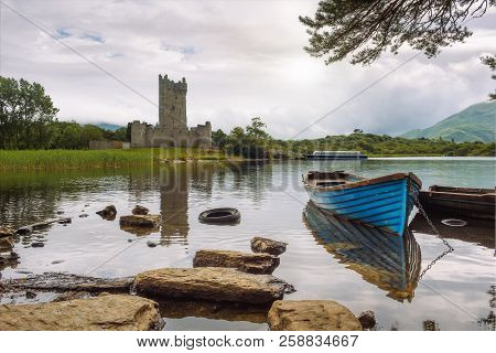 Ross Castle Ruins And The Lough Leane Lake With A Blue Boat In The Foreground In The Killarney Natio