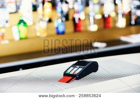 Red Bankcard Inserted In Reader On Defocused Background