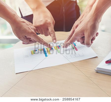 Business Group All Agree And As A Team Pointing The Hand At Graph Paper, Graphs, And Financial Stati