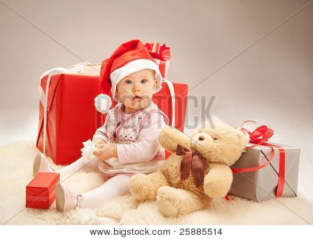 Surprised baby siting with gift boxes and a teddy bear