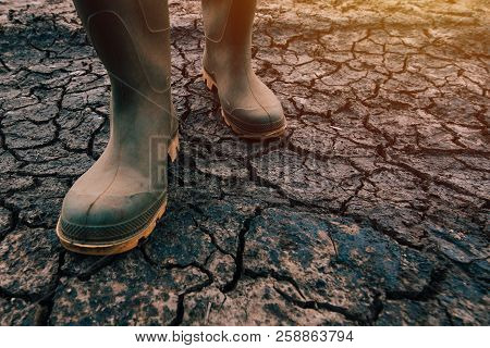Farmer In Rubber Boots Walking On Dry Soil Ground, Global Warming And Climate Change Is Impacting Cr