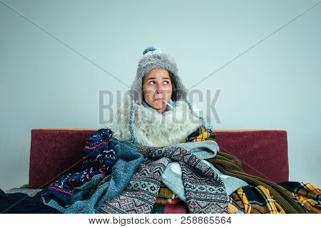 The Young Sick Woman With Flue Sitting On Sofa At Home Or Studio Covered With Knitted Warm Clothes.