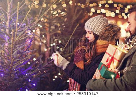 Adult couple shopping for Christmas tree in the city during Christmas time