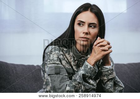 Close-up Portrait Of Thoughtful Female Soldier In Military Uniform With Ptsd Sitting On Couch And Lo