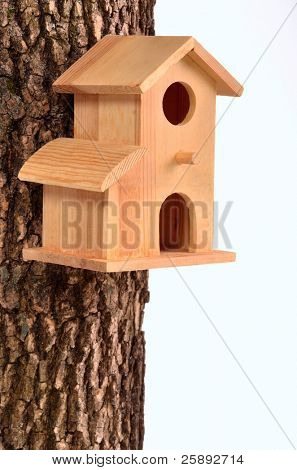 Comfortable starling-house on a tree trunk isolated on white background