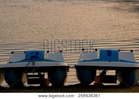Pedal Boats Parked On The Shore Of The Lipno Dam At Sunset.the Summer Evening By The Water - Pedal B