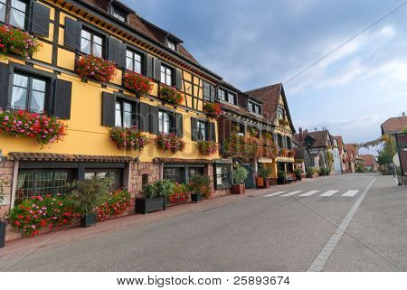 Empty street in Alsace with yellow half-timbered house with flowers poster