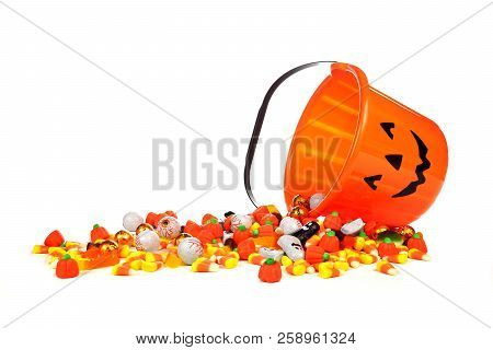 Spilling Halloween Jack O Lantern Candy Collector With A Pile Of Candy Over A White Background