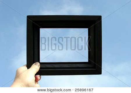 a black picture frame is held against a blue sky by a real human hand