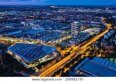 MUNICH, GERMANY - JULY 08, 2018: Aerial view of BMW Museum and BWM Welt and factory and Munich from Olympic Tower illuminated at night. BMW is a famous German luxury car automaker.