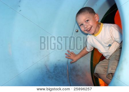 my almost 3 yr old grandson smiles while playing in a plastic slide poster