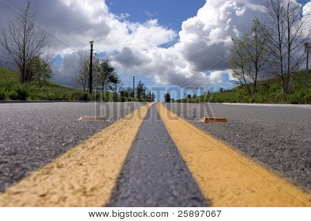 a  two lane road with a blue sky and white fluffy clouds