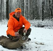 hunter in safety orange with a whitetail deer harvested against a snow and tree background poster