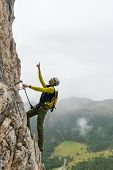 young attractive male mountain climber on a steep and exposed Via Ferrata in Alta Badia in the South Tyrol in the Italian Dolomites pointing to the summit poster